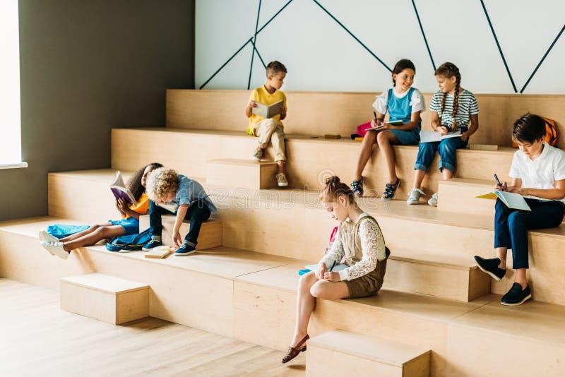 有笔记本的学童学习在木论坛的小组  免版税图库摄影