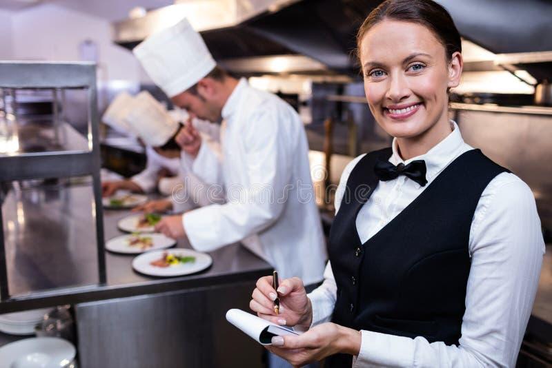 有笔记本的微笑的女服务员在商业厨房里 免版税库存照片