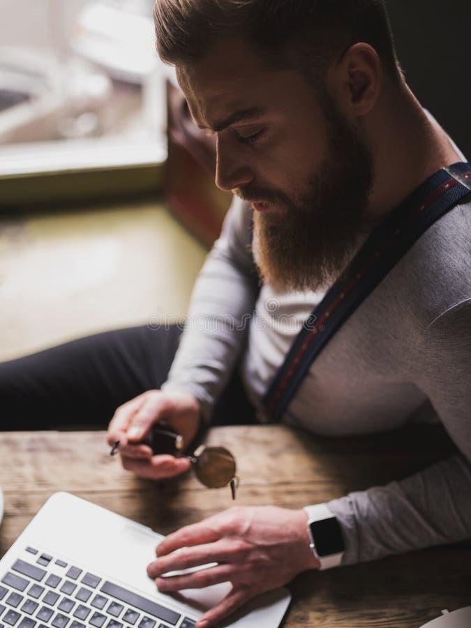 有笔记本的快乐的年轻有胡子的人 免版税图库摄影