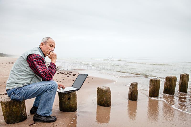 有笔记本的老人在海滩 免版税库存照片