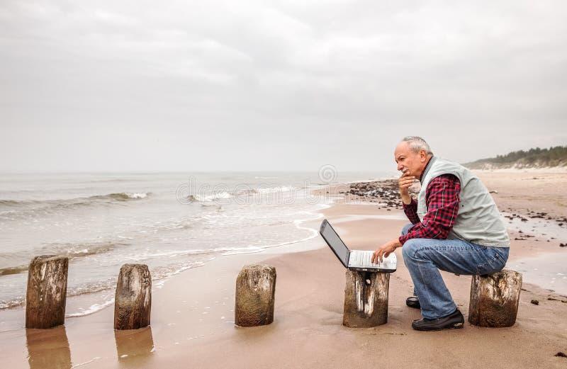 有笔记本的老人在海滩 图库摄影