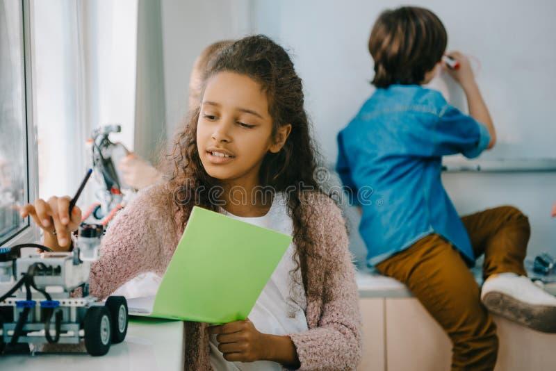 有笔记本的青少年的非裔美国人的女小学生在词根 免版税库存图片