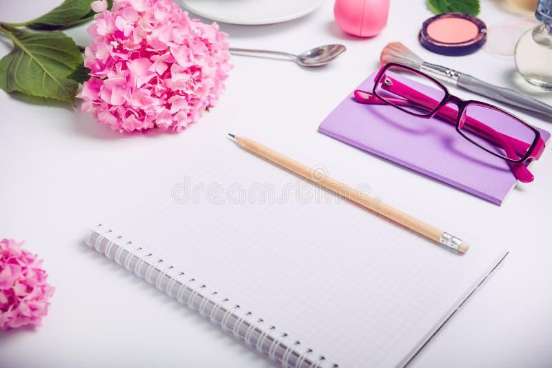 有笔记本的顶视图女性工作地点计划,化妆辅助部件、写生簿、玻璃和紫藤花的在w 免版税库存照片