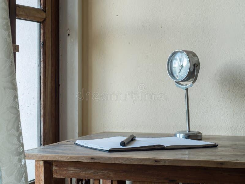 有笔记本的,笔,在一张木桌上的时钟工作场所 免版税库存照片