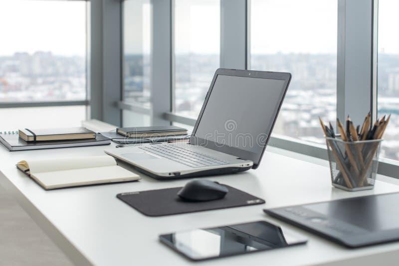 有笔记本膝上型计算机舒适的工作表的工作场所在办公室窗口和城市视图 库存照片
