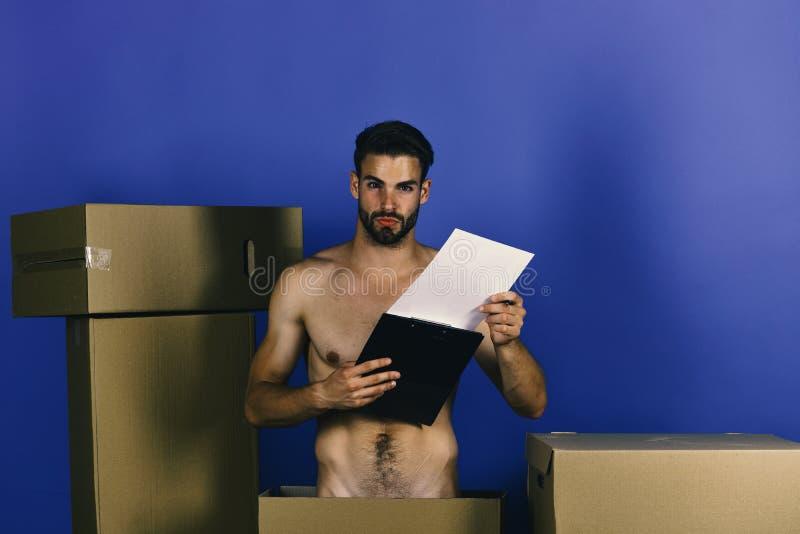 有笔记板的人在纸板箱中 性别和交付概念:有笔记板的赤裸人 免版税库存图片