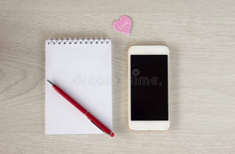 有笔记薄、红色笔和小心脏谎言的白色电话在一张白色木桌上 库存照片