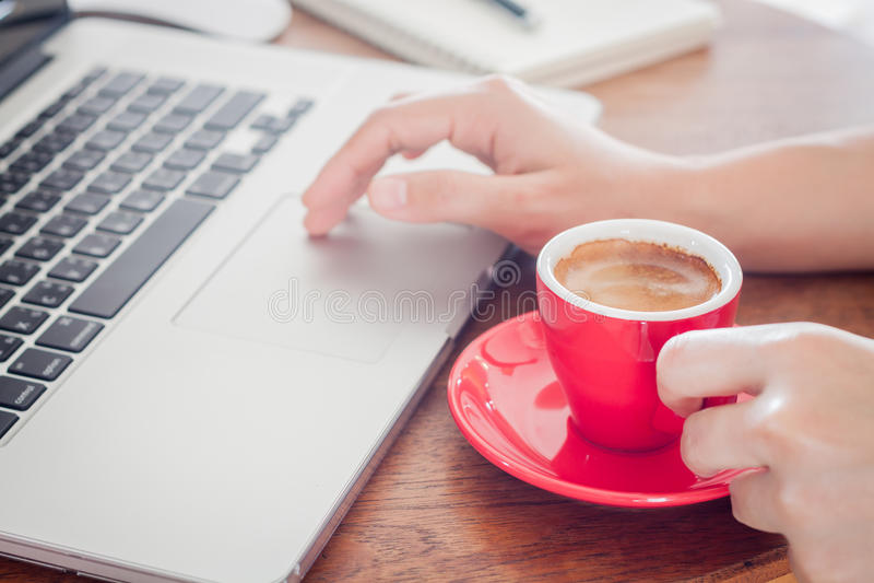有笔记薄和膝上型计算机的红色咖啡杯 免版税库存照片