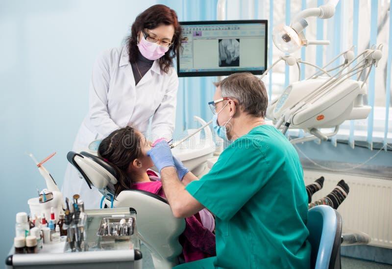 有第一次牙齿参观的女孩 有对待耐心牙的护士的资深小儿科牙医在牙齿办公室 免版税库存图片