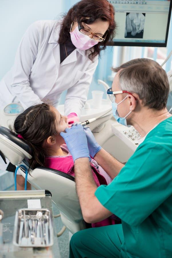 有第一次牙齿参观的女孩 有对待耐心牙的护士的资深小儿科牙医在牙齿办公室 免版税库存照片