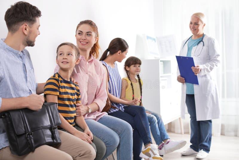 有等待他们的轮的孩子的父母 参观的医生 免版税库存照片