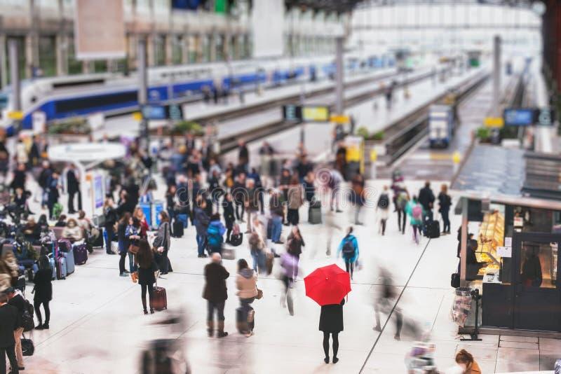 有等待在火车站的红色伞的妇女 免版税库存照片