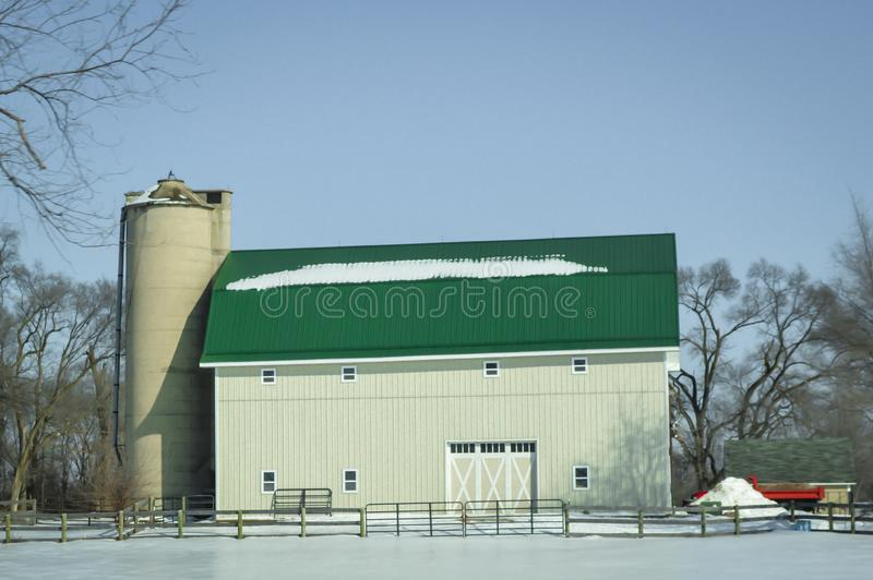 有筒仓的大白色绿色屋顶谷仓在冬天雪 图库摄影