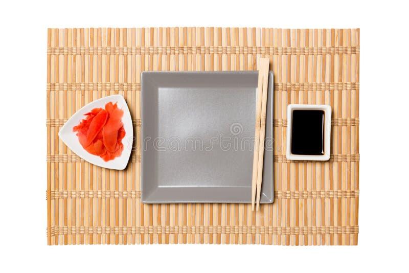 有筷子的空的灰色方形的板材寿司、姜和酱油的在黄色竹席子背景 r 免版税库存图片