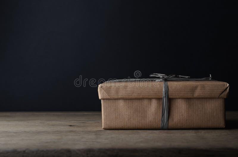 有简单的包装纸和灰色酒椰丝带的礼物盒 免版税图库摄影