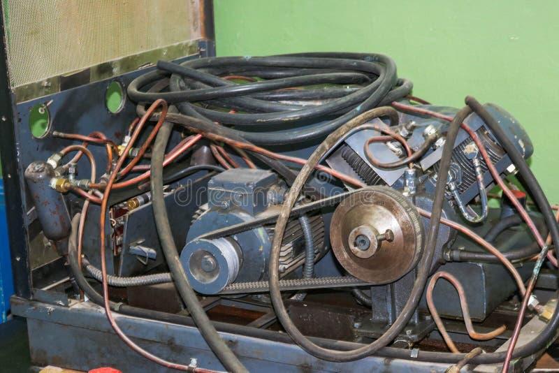 有管和水管的老异步电动机,皮带传动在一套工厂设备 免版税库存照片