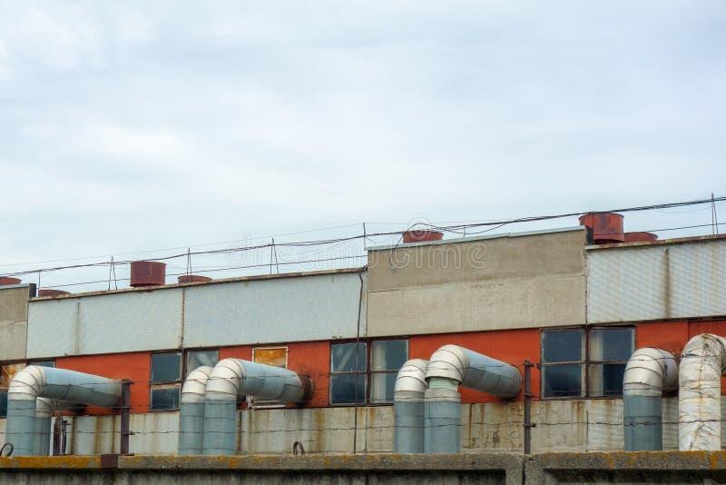 有管子和管的产业植物 制造的复合体外部看法在蓝色云彩天空下 混凝土墙,金属框架, 库存图片
