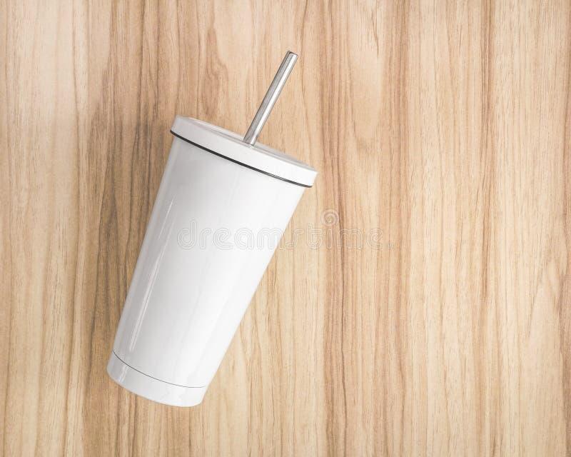 有管的白色钢杯子在木背景 被绝缘的容器为保留您的饮料 库存图片
