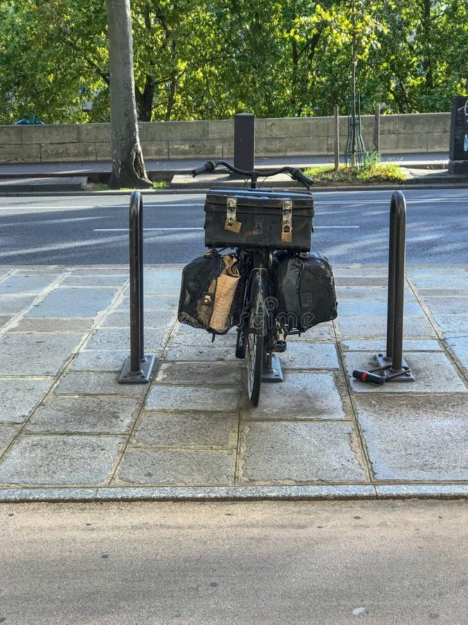 有箩的黑自行车和在巴黎街上的古老箱子 免版税库存照片
