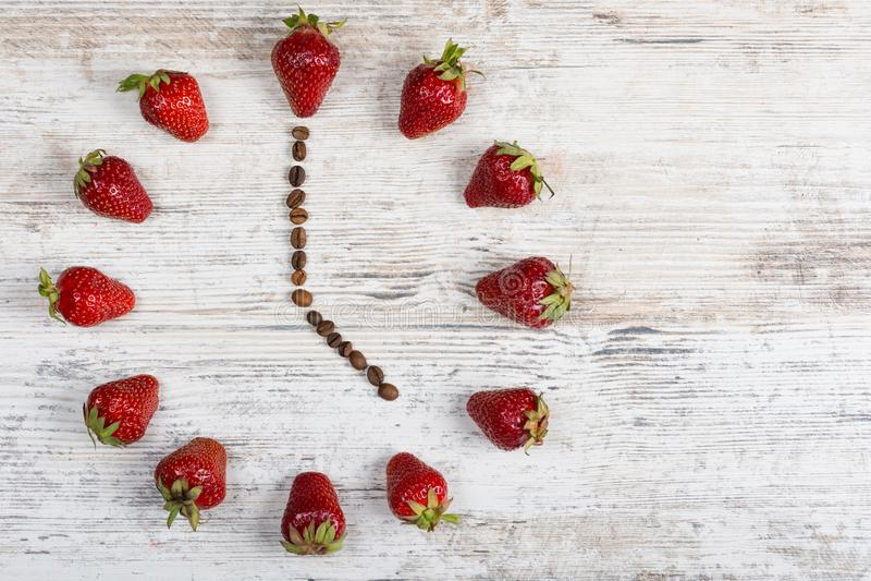 有箭头的一个草莓时钟从显示五个或十七个小时的时期在一张木葡萄酒桌上的咖啡豆在kitche 免版税库存照片