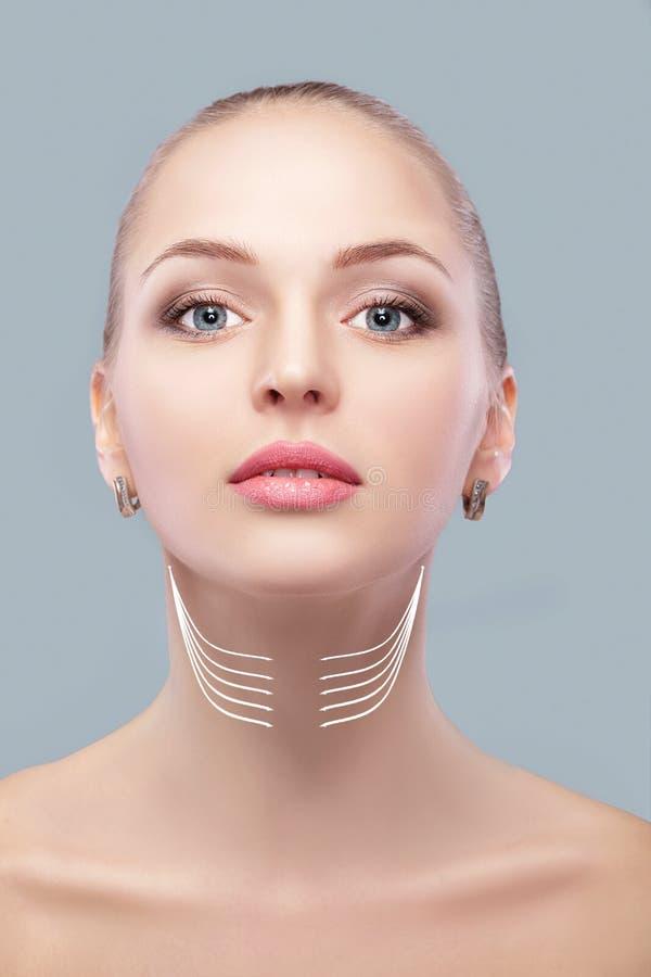 有箭头的妇女在面孔脖子举的概念 双下巴的更正 免版税库存图片