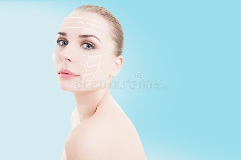 有箭头的美丽的妇女在她完善的被修饰的面孔 图库摄影