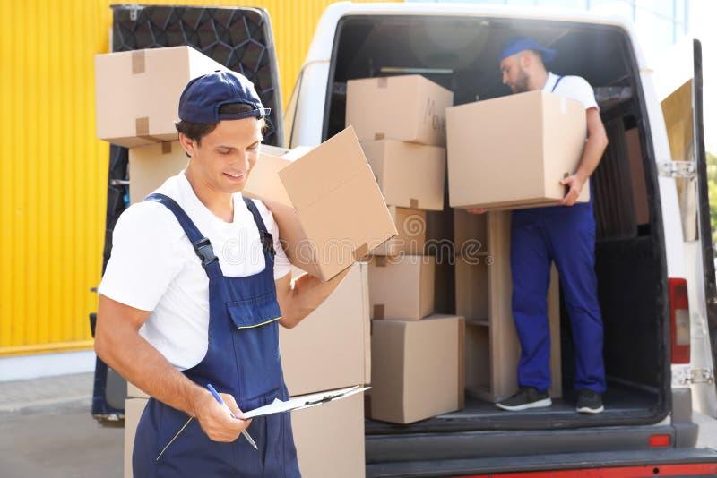 有箱子和剪贴板的公搬家工人 免版税库存图片