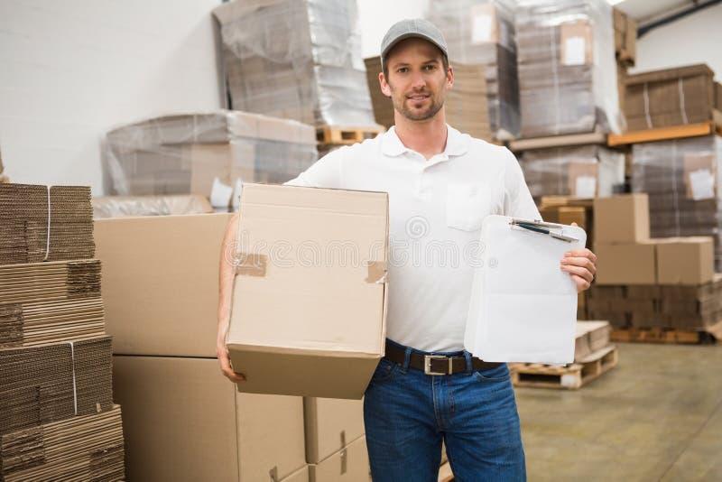 有箱子和剪贴板的送货人在仓库里 库存图片