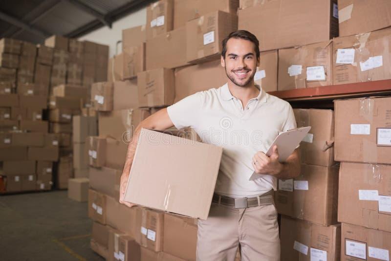 有箱子和剪贴板的送货人在仓库里 图库摄影