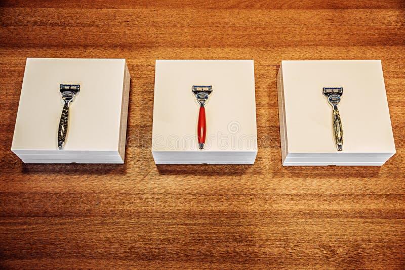 有箱子的三把时髦的剃刀在木桌上 免版税库存照片