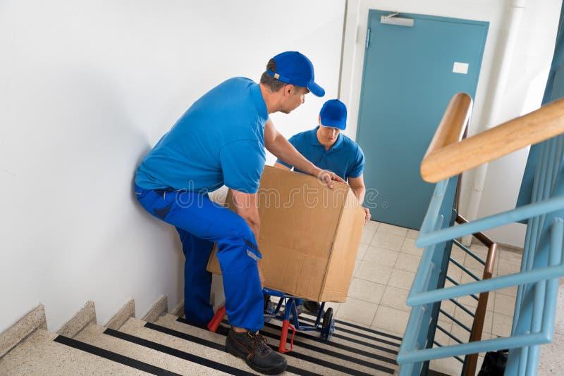 有箱子的两名搬家工人在楼梯 库存照片