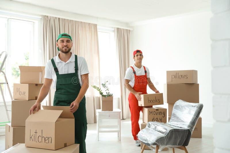 有箱子的公搬家工人在房子里 库存照片