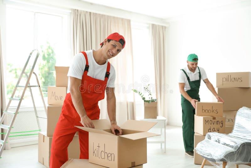 有箱子的公搬家工人在房子里 免版税库存图片