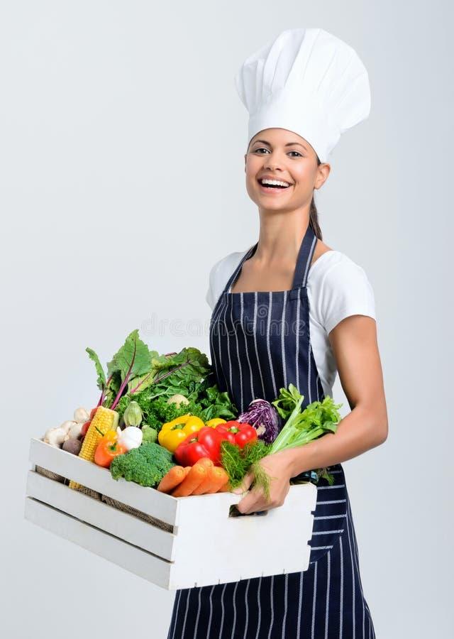 有箱子的厨师有很多未加工的蔬菜 免版税库存图片
