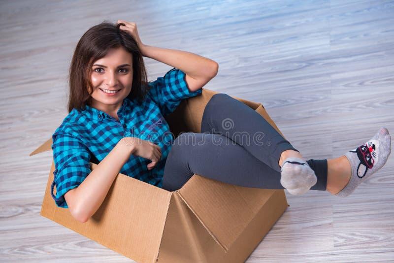 有箱子的少妇在移动的房子概念 库存照片