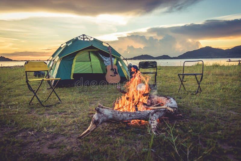 有篝火的野营的帐篷在绿色领域草甸、湖和山背景 野餐和旅行概念 o 免版税库存图片