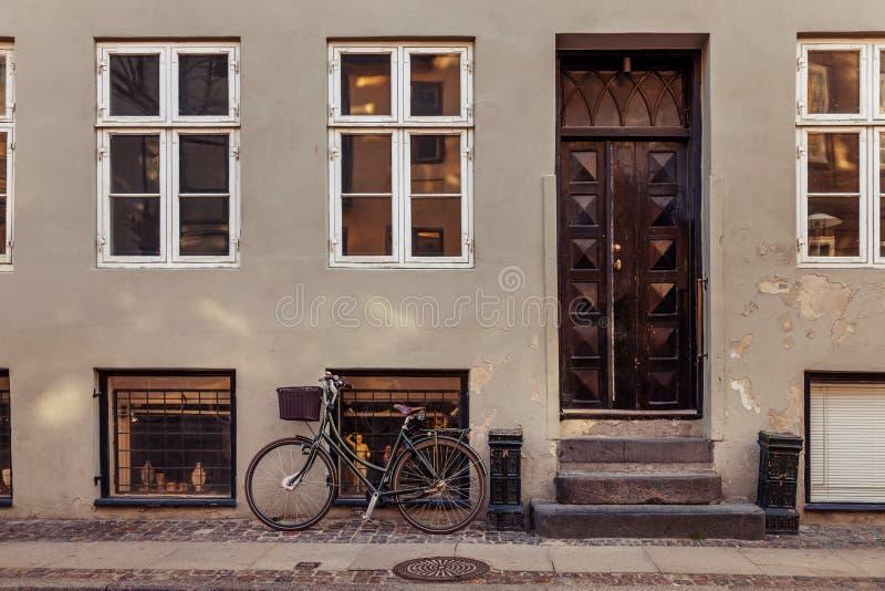 有篮子的停放的自行车在与闭合的门的灰色大厦附近在街道上 免版税库存图片