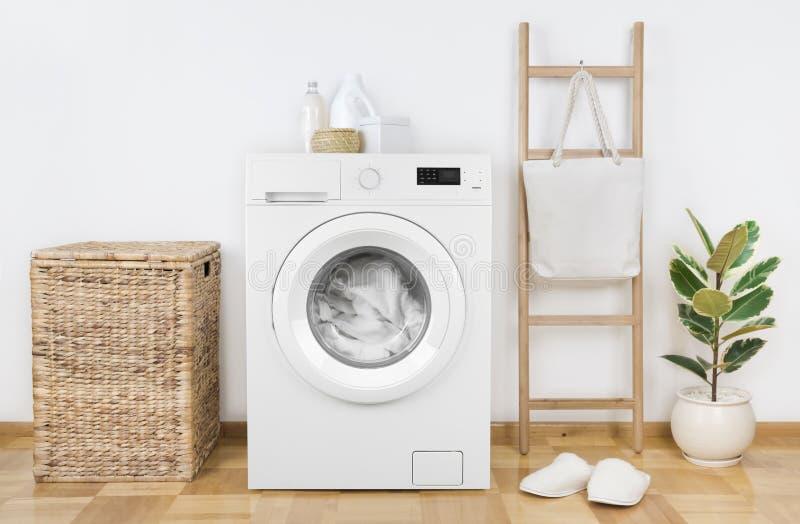 有篮子的现代洗衣机在洗衣房内部 免版税库存照片