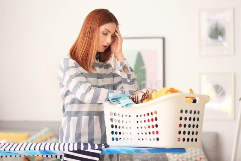 有篮子的疲乏的主妇有很多衣裳 免版税库存图片