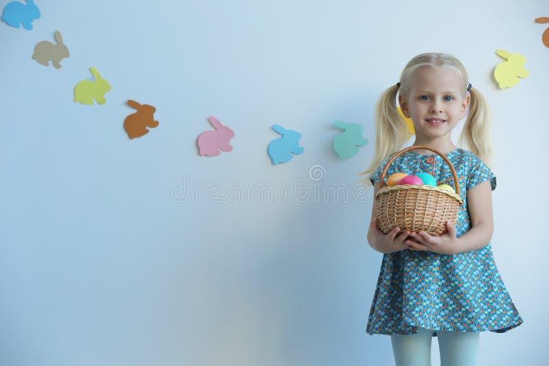 有篮子的逗人喜爱的小女孩有很多复活节彩蛋 库存图片
