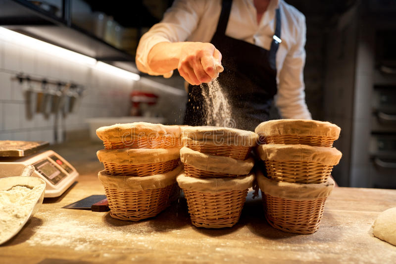 有篮子的贝克上升在面包店的面团的 库存图片