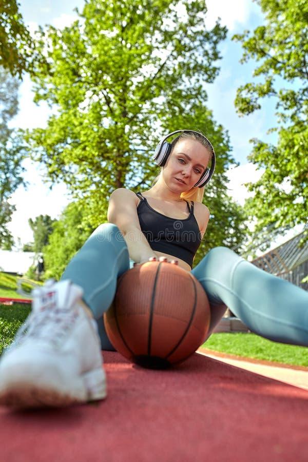 有篮球球的美丽,运动女孩听到与耳机的音乐 体育刺激,健康生活方式 免版税库存图片