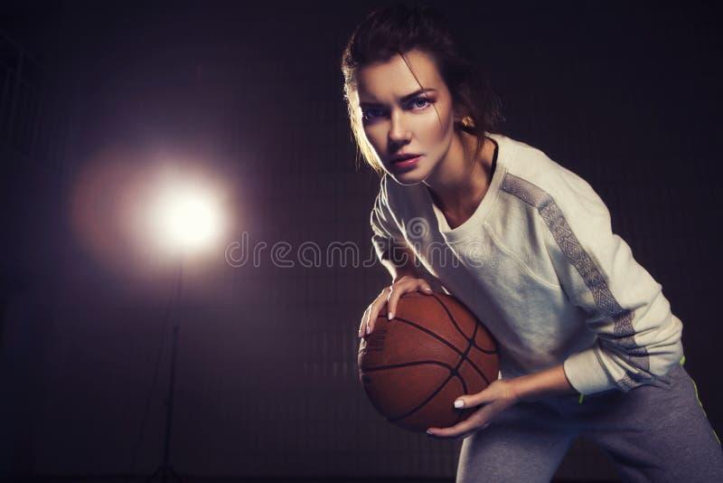 有篮球球的适合的亭亭玉立的年轻美丽的深色的妇女 免版税库存图片