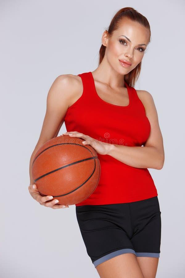 有篮球的可爱的妇女 免版税库存图片
