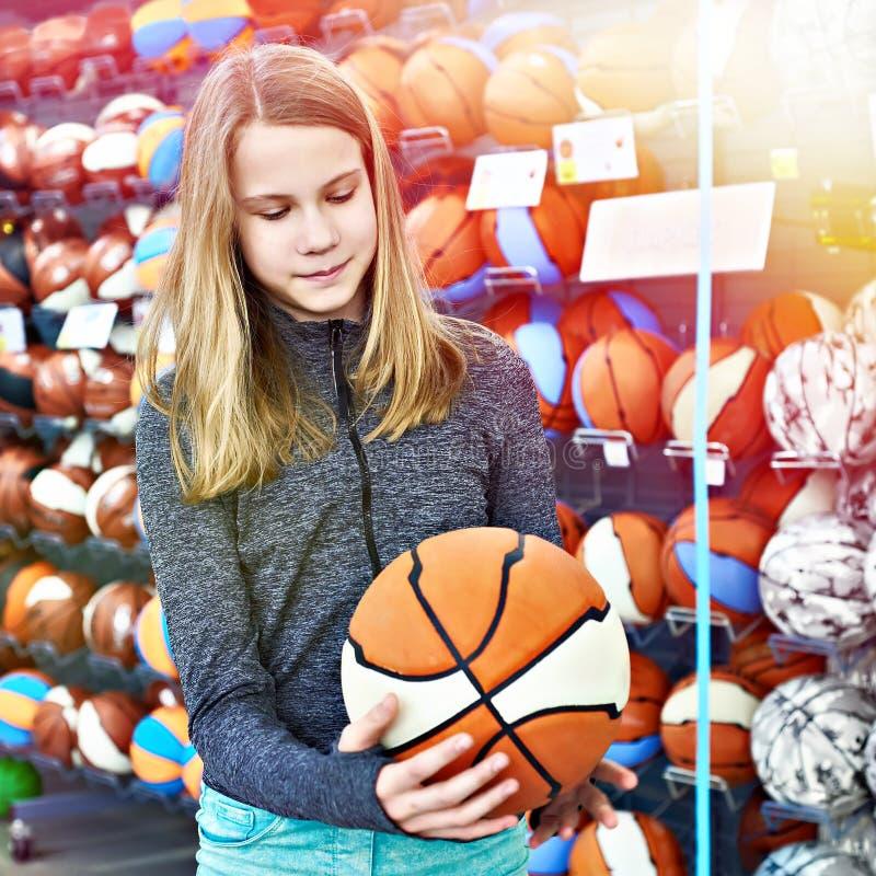 有篮球的女孩在体育商店 免版税图库摄影