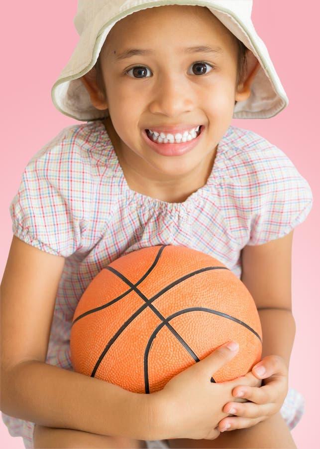 有篮球的小逗人喜爱的女孩 免版税图库摄影