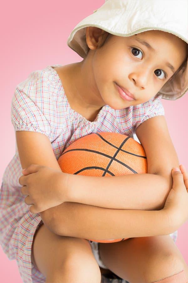 有篮球的小逗人喜爱的女孩 免版税库存照片