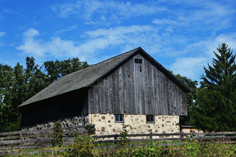 有篱芭的石和木谷仓 库存照片