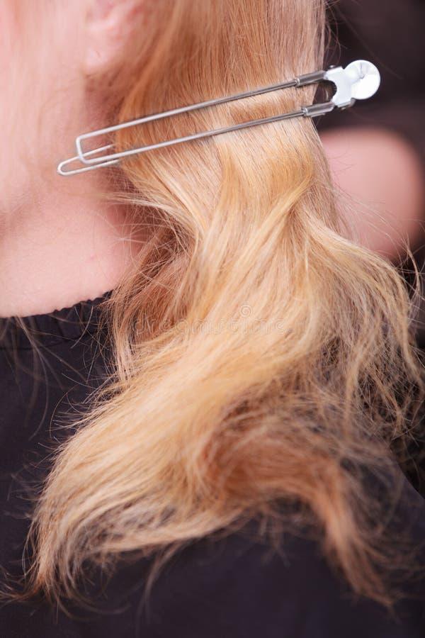 有簪子别针的女性金发。由美发师的妇女美容院的 图库摄影