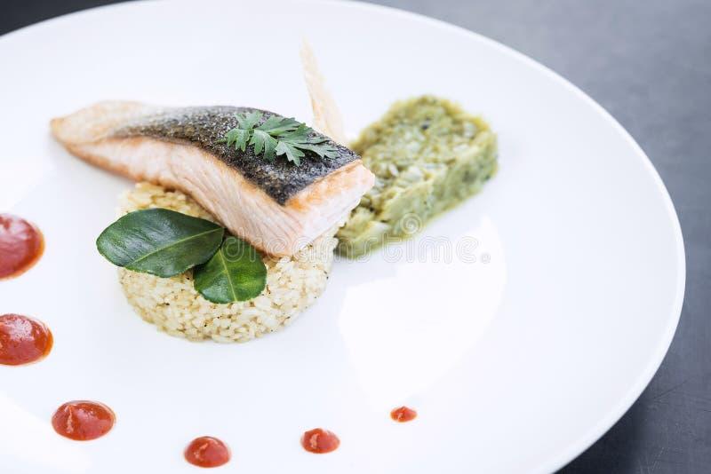 有米和鳄梨调味酱捣碎的鳄梨酱膳食的食家三文鱼鱼片 免版税库存照片